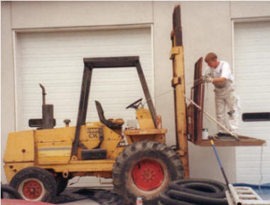 Worker uses long handle to operate controls of fork truck